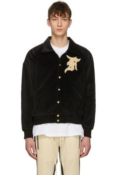 Long sleeve padded cotton corduroy bomber jacket in black. Spread collar. Press-stud closure at front. Terrycloth appliqué in beige and black at chest. Welt pockets at waist. Raglan sleeves. Rib knit cuffs and hem. Quilted silk lining. Gold-tone hardware. Tonal stitching. Available exclusively at SSENSE.