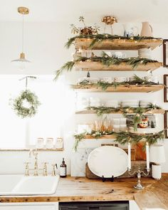 open shelving in the kitchen decorated with greenery and white christmas lights.