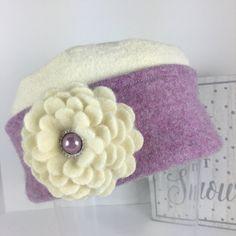Dieser Hut ist ein Unikat, hergestellt aus einen wunderschönen Creme Merino Wolle Pullover und eine Orchidee lila Kaschmir, liebevoll gerettet, gefilzt und koordiniert in meinem Studio. Die geschichteten Kaschmir Blumenbrosche ist abnehmbar und kann auf die Manschette des Hutes oder anderswo um sicherzustellen, dass Ihre neue Hut mit vielen verschiedenen Outfits paar wird getragen werden.  Meine Hüte sind One size fits all, aber jeder Pullover Kombination ist anders. Dieser fühlt sich ein…