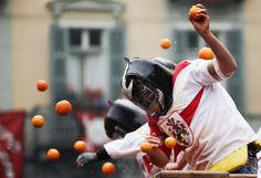 2015 | CARNAVAL DE LAS NARANJAS, EN IVREA, ITALIA - Members of rival teams fight with oranges during an annual carnival battle in the northern Italian town of Ivrea on February 15, 2015. Dressed up as Middle Age kings' guards, a group of men ride in a horse-drawn carriage and pelt 'foot soldiers' with oranges as thousands of people gather to re-enact a Middle Age battle when the townsfolk of Ivrea overthrew an evil king.