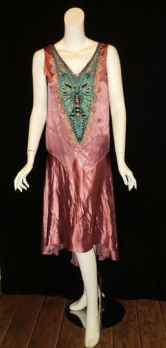 "1920s drop waist Art Deco flapper dress embellished with a hand-beaded dragonfly panel and trimmed with a plum and green ""shell"" design trim. This piece was hand dyed using a distressed process enhancing the age and character of this lovely shade of plum pink.  This is an original Bellasoiree Original.  Via Salon of the Dames."