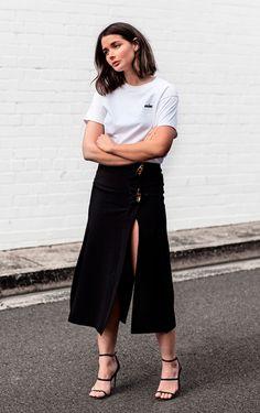 Street style look com camiseta branca, saia preta fenda e sandália.