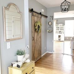 I Spy Antique Farmhouse in this beautiful entry way full of architectural detail & #farmhouse charm. Love that sliding barn door feature! #homedecor
