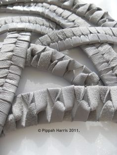 Textiles design using strips of leather to create a twisted interlocking structure - fabric manipulation techniques; leather strap design // Pippah Harris