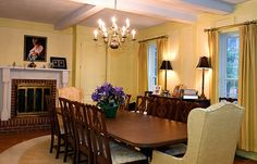 Dining room with yellow walls, exposed beams, floor-to-ceiling windows, fireplace.