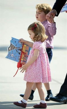 July 21, 2017: Princess Charlotte clutches her in-flight entertainment, a farewell gift from her visit to Germany, as she and Prince George board their flight home. A helping hand from Daddy Prince William for Princess Charlotte who wouldn't let go of her new books. #RoyalVisitGermany (Tumblr)..
