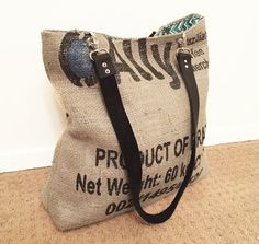 Made from an up-cycled burlap coffee sack, this eco-friendly tote bag includes one open interior pocket and secures with a silver magnetic snap