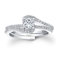 This classic white gold interlocking diamond wedding ring set, features a prong set round diamond center. The engagement ring is set with pave set diamonds and splits to allow the pave set diamond wedding band to slip into the engagement ring under the center.<br /> <br /> Also available in rose or yellow gold, 18k and Platinum.