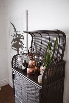 Mid Century Minimal Rustic Dining Room // black rattan bar cart, black and white art, copper mugs, snake plant