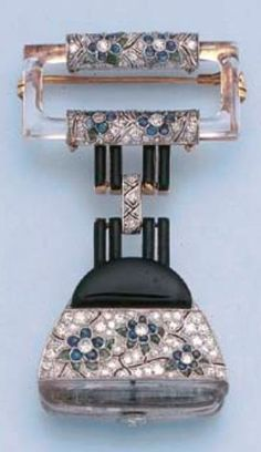 """rubies.work/… AN ART DECO DIAMOND, ONYX AND GEM-SET LAPEL WATCH, CIRCA 1920. Designed as a pavé-set diamond """"handbag"""" with sapphire and emerald floral decoration to the onyx top, with white dial and Arabic numerals to the reverse, suspended from enamel and diamond vertical lines to the rock crystal, diamond and gem-set openwork flower brooch, 5.6 cm. long."""