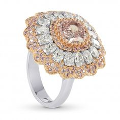 Simply breath-taking...A 1.63Ct Fancy Orangy Pink cushion diamond certified by GIA, mounted in platinum and 18K rose gold, with fancy pink and collection white oval side diamonds. The cushion diamond is set with micro-prongs and is immediately surrounded with a fancy pink round brilliant pave set halo, giving the center diamond and even larger appearance. The middle halo is set with 16 collection color white ovals 1.41Ct TW. The inner halo and outer floral halo are set with 178 fancy pink…