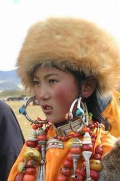 Tibet | Girl in Yading, wearing traditional style earrings and necklaces from…