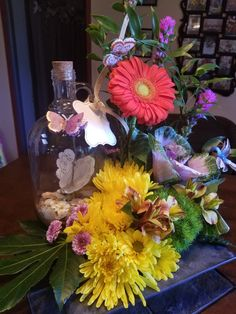 Message in a bottle arrangement with bright flowers and newspaper butterflies.  Arranged in a slate square it also has a hummingbird. Inside the bottle is decorative sand, seashells and paper flowers. This is unique for a man or woman. #messageinabottle #bottlecenterpieces #Mothersday #Fathersday #sympathyflowers #mesaflowershop #mesaflorist #newspaperbutterflies #seashellsandsand