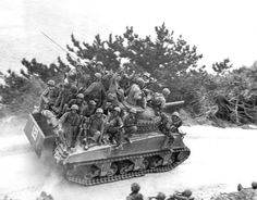 Tank-borne infantry moving up to take the town of Ghuta before the Japanese can occupy it. The men are members of Colonel Victor Bleasdale's 29th Marines.