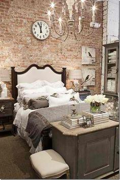 La pared de ladrillo ofrece un marco ideal para la cama con lencería en blanco y gris y los muebles patinados. Atención a la cómoda a los pies de la cama