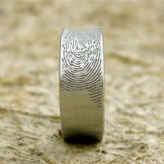 His wedding band with her fingerprint. -such a cute idea, would be great for both bands!