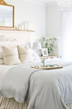 White cottage style bedroom accented with blue and white grain sack pillows and a blue and white seersucker comforter