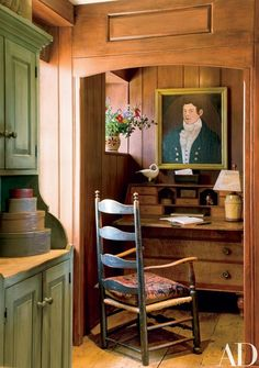 In the kitchen's small office area, a 19th-century portrait in its original frame hangs above a desk made of pine and tiger maple | archdigest.com