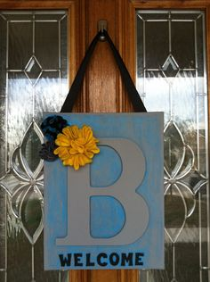 A couple of ideas that I put together from Pinterest to make this for my front door. Canvas, wooden letter, acrylic paint, felt flowers, ribbon, and felt scrapbook letters. all from Hobby Lobby and very inexpensive to make.