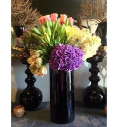An arrangement of hydrangea, tulips, stock flower, roses, allium and lilies in a tall sleek black vase.