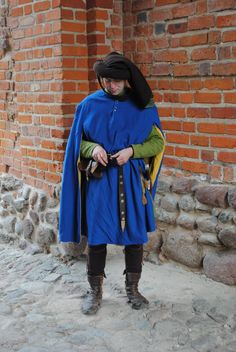 Outfit of an English knight, beginning of the 15th century. High boots, woollen hose, linen braie and shirt, robe of green wool and houppelande of blue wool with yellow linen lining, chaperon. All parts are completely hand-sewn. Plus belt and other period accessories attached to it. Photo taken in Czersk Castle, Mazovia, Poland