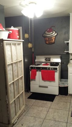 Gray, red, and yellow kitchen with antique stove.