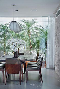 Sala de jantar | Mesa de madeira de demolição e cadeiras com couro, da Way Design. Luminárias de Fernanda Vasconcellos. Na parede, revestimento de mármore travertino da Palimanan. Ao fundo, o pequeno jardim de palmeiras recebeu o banco de ripas de cumaru. (Foto: MCA Estúdio)