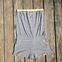 Aqua Brand Grey w Yellow Trim Strapless Romper Aqua Brand Grey w Yellow Trim Strapless Romper w pockets and yellow detail trim ... Stretchy material and uber comfy ... Tie around bust for adjustability Aqua Other