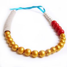 Moldarina.... One-of-a-kind, this beaded necklace is handmade with wood beads (hand painted in red, gold and metallic white), linen and turquoise ribbon.  www.moldarina.com