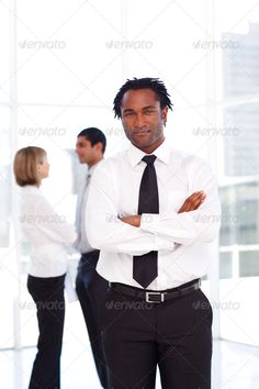 African businessman with folded arms with his team in the backgr ...  adult, african, american, arm, arms, beauty, black, business, businessman, businesspeople, businessteam, businesswoman, confidence, confident, contact, corporate, crossed, cut, decision, executive, folded, friendly, happiness, happy, indoor, male, man, management, men, one, outdoor, person, portrait, professional, smile, smiling, standing, studio, success, suit, team, young