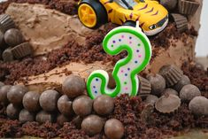 a white and green number 3 birthday candle on a monster truck cake with malt balls as rocks