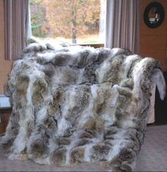 Coyote Fur blanket. I think fur off-sets the cold stone and dark wood well. Makes it both manly and cozy.