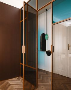Petrol blue appears again in the gridded partition stands at the back of the room, which comprise a mix of coloured and transparent panes of glass. Timber Battens, Timber Walls, Wooden Flooring, Concrete Floors, Apartment Walls, Copper Handles, Marble Showers, Glass Brick, Translucent Glass