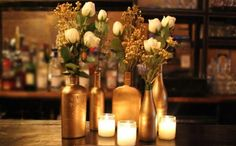 Could do in gold or bronze and just have plain votives. Use real flowers in the bottles.  Simple and inexpensive.
