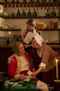 Barmaid and bartender try to get a British officer to talk more than he should in the Raleigh Tavern's bar. 18th Century scene in historic Colonial Williamsburg, Virginia. Photo by David M. Doody.