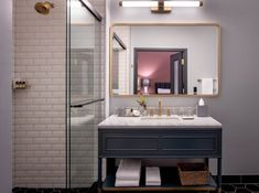 Bath Room, Marble Counter, Porcelain Tile Floor, Enclosed Shower, Undermount Sink, Wall Lighting, and Subway Tile Wall The elegant bathrooms are finished with white beveled subway tile, marble countertops, and brass Kohler fixtures.