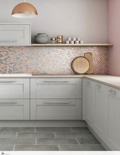 This on trend blush copper and metallic mosaic tile shot has a refined sophisticated look. The simple light grey shaker kitchen doors are teamed with slate grey floor tiles and a solid quarts worktop. Shaker Kitchen Doors, Grey Shaker Kitchen, Grey Kitchen Cabinets, Shaker Cabinets, Kitchen With Grey Floor, Pink And Grey Kitchen, Grey Cupboards, Grey Shelves, Copper And Grey Kitchen