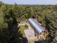 valbæk brørup architects has completed a wooden summer house in denmark with a vaulted steel roof and an extruded tube shape. Wooden Summer House, Wooden House, Architect House, Architect Design, Dark Blue Kitchens, Quonset Hut Homes, Agricultural Buildings, Summer Cabins, Wooden Cabins