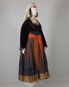 Women's costume of Psara, North-East Aegean Islands Early 20th century ©Peloponnesian Folklore Foundation, Nafplion, Greece The women's costume of Psara belongs to a type that appears to have been worn in varying forms on other Aegean islands as well. It is renowned for its pure silk tsiboukotó chemise. The dark sleeveless dress has a richly-pleated skirt with the characteristic horizontal pleat about 20 centimetres above the hem, which has a decorative strip of brocade. This horizontal…