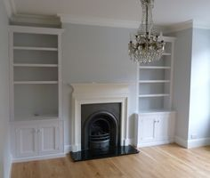 Here's how this part of the room could look, with built-in cupboards below the shelves, cornicing and the fireplace painted white. A central chandelier would look good too