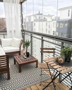 como decorar una terraza pequeña, balcón con suelo de madera y tapete, muebles de madera, cojines blancos, mesa con candelas y plantas