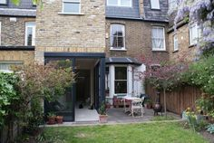 Three storey Victorian terraced house with contemporary kitchen extension with floor to ceiling glass walls opening out onto a patio and garden. Victorian Terrace House, Victorian Homes, Glass Extension, Extension Ideas, London Architecture, Home Upgrades, House Extensions, Home Additions, Exterior Design