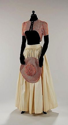 1940 Summer dress by Elsa Schiaparelli. The choice of red and white striped cotton for the short bolero and matching hat is reminiscent of striped beach cabanas.