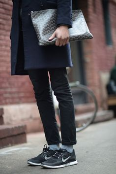 Keeping casual with black denim, sneakers, and an oversized Goyard Senat clutch.