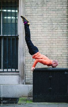 Young man doing urban street yoga. by kkgas