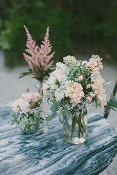 reception tables - half and half  mix of 3-4 glass containers with coordinating flowers, small candle votives (gold), wood table # and wood slab under one of the glasses