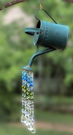 Put this rustic watering can sun catcher in your yard and add a little wow & pizzazz! Strung with beautiful blue & green peacock colored acrylic beads and clear acrylic water drop beads. Really dazzles & sparkles when the sun hits the clear beads! A Willow Tree Loft one-of-a-kind item. - Overall hanging height: approx 31 - Watering can  * handle to spout: 16  * 11 tall  * 6.5 wide - 12 strands of acrylic beads strung on 50 lb. mono-filament