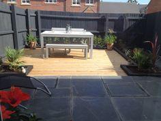 My Urban Garden; grey fence, decking, black sleepers, grey fence, grey slabs and a grey table with palms & solar jar lights