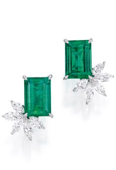 Pair of 18 Karat White Gold, Emerald and Diamond Earclips.  Set with two emerald-cut emeralds weighing 6.64 and 6.42 carats, accented by marquise-shaped diamonds weighing approximately 2.35 carats, signed Bellini.