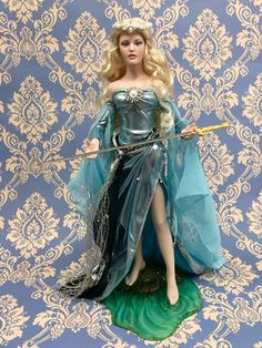 "Lady of the Lake. An enchanted vision from the age of Camelot. She rises from the watery depths to bestow the legendary sword Excalibur upon the man who would be king, Arthur. This exquisite spirit of the lake is crafted of fine, band-painted porcelain. Magnificently dressed in lame and chiffon that shimmers in the color of crystalline waters. And in her delicate hands she bears d gleaming sword-Excalibur! Approx. Inc 18"" (44cm)"